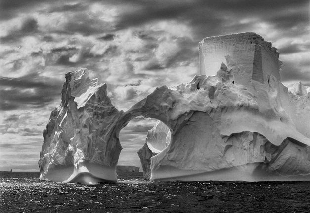 Sebastião Salgado, Iceberg between Paulet Island and the South Shetland Islands on the Antarctic Channel. At sea level, earlier flotation levels are clearly visible where the ice has been polished by the ocean's constant movement. High above, a shape resembling a castle tower has been carved by wind erosion and detached pieces of ice. The Antarctic Peninsula, 2005. © Sebastião Salgado/Amazonas images—Contact Press Images.