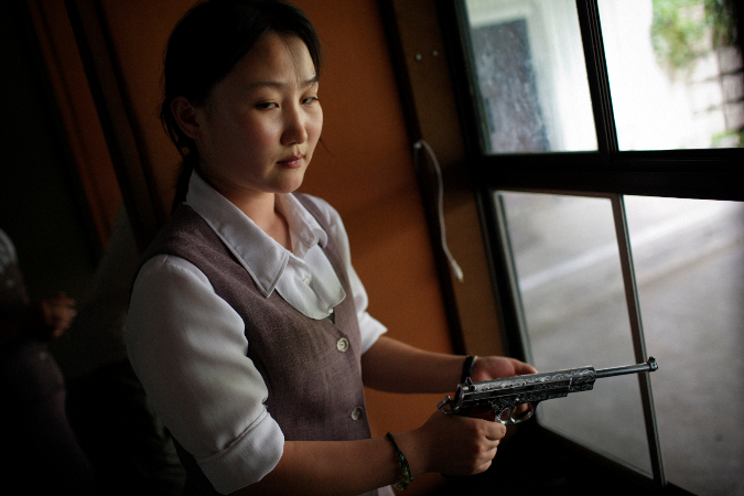 Tomas van Houtryve, A North Korean woman loads a pistol for firing practice in Pyongyang, North Korea, 2007
