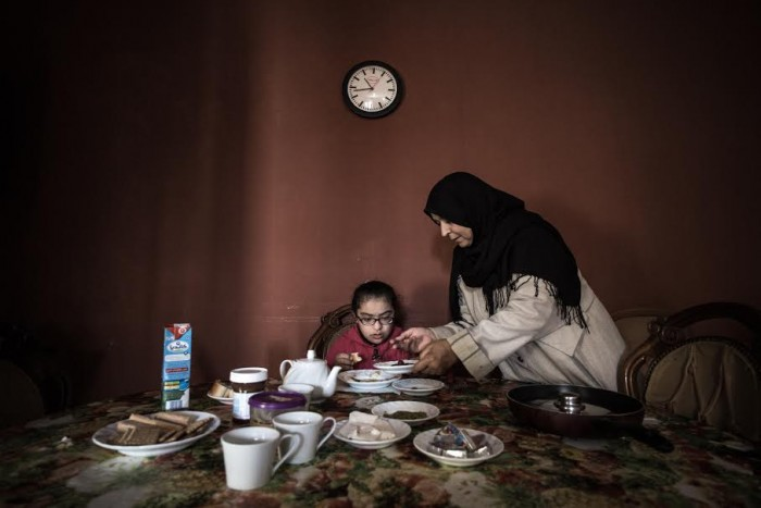 © Mohamed Alalem, for Reporting Change. Shahd. Shahd's mother serves her breakfast, at home in Tripoli.
