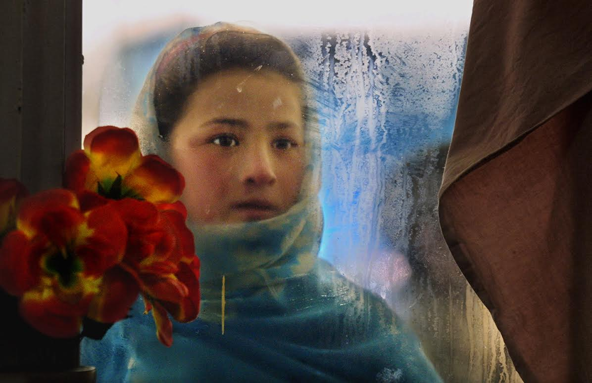 A girl looks through the frosted window of a restaurant, hoping to get leftovers. She begs after school to help out her family. (Kabul, January 13, 2002)