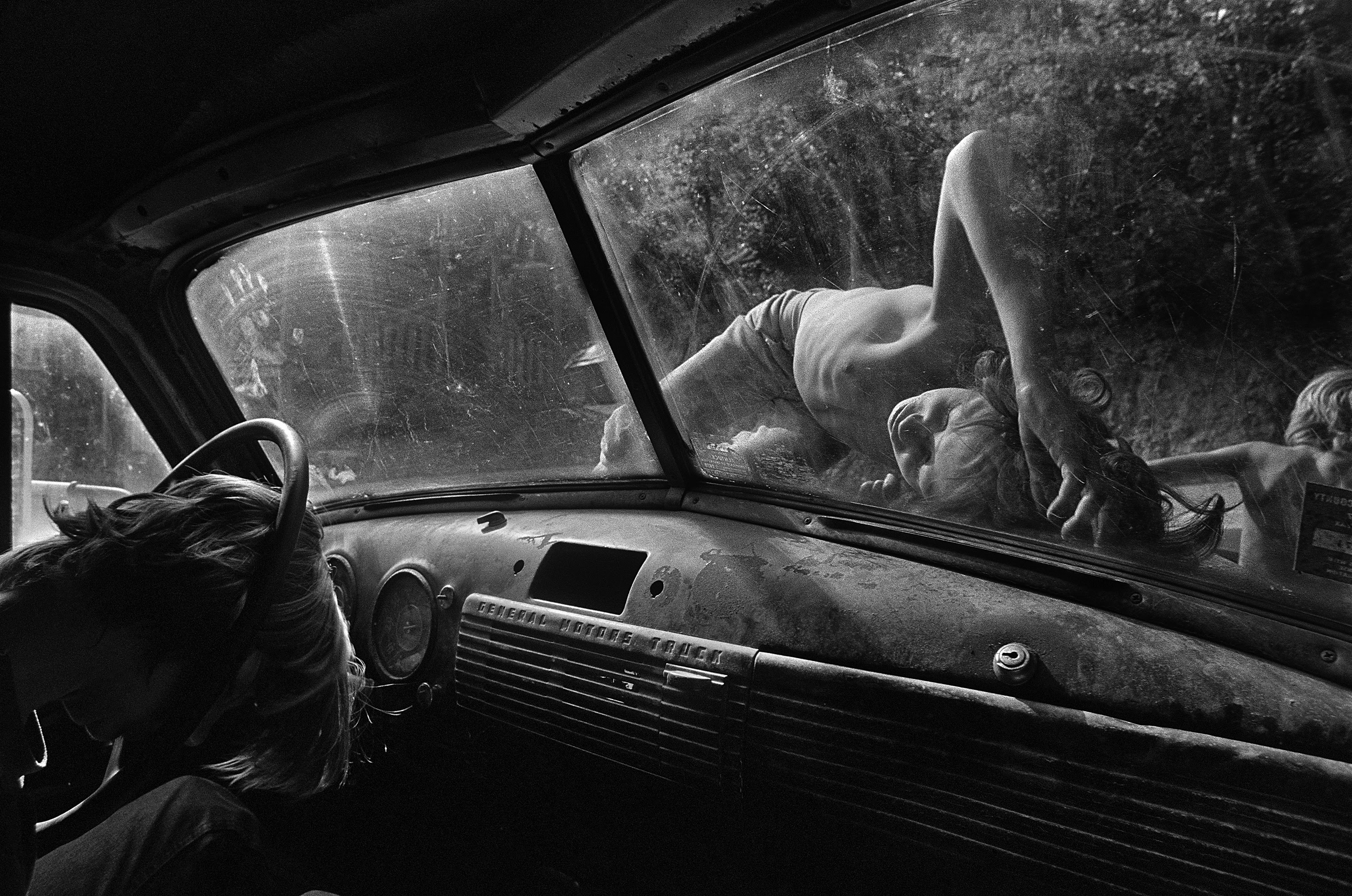 Caption: Boys sleep on the hood of a pickup truck on a hot summer day in Still House Hollow, Tennessee.Title: Still House Hollow, Tennessee, 1986